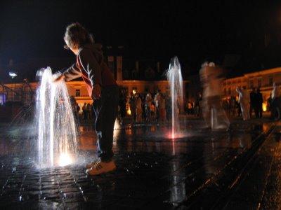 Copil care se joaca cu apa in timpul concertului din Piata Mare